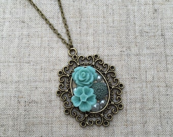 Pendant necklace with dusty antique-blue flowers and pearls.