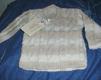 A hand knitted cable pattern jumper