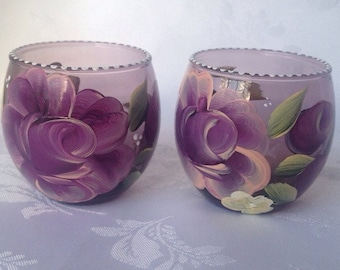Set of 2 hand painted candle holders with roses on a cranberry glass
