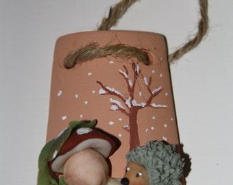 Decorative terracotta shingle representing an hedgehog