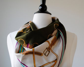 a vintage scarf. olive green ivory pink yellow and turquoise western style with belt graphic print.