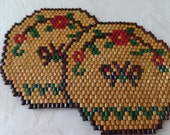 Pair of vintage trivets made from wooden beads with flowes and butterflies