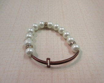 Pearl white beaded bracelet with copper hollow sideway cross.