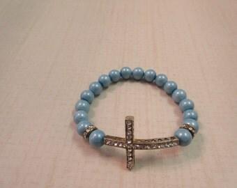 Blue beaded bracelet with silver sideway cross.
