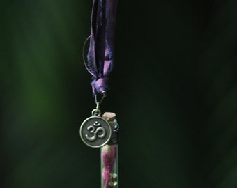 The Valkyrie's Heart. Rosebud, Rose Leaf, and Peridot in Glass Vial on Vintage Sari Silk with Om Charm Necklace