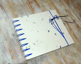 Unique Guestbook with handmade blue flower paper in Secret Belgian Binding with blue satin tapes