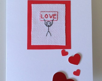 Cross stitch card of a stick man holding up a Love sign with red heart detail