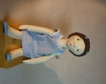 Doll articulated earthenware as formerly. Blue gingham dress.