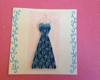 Card with blue party dress on hanger, made by quilling
