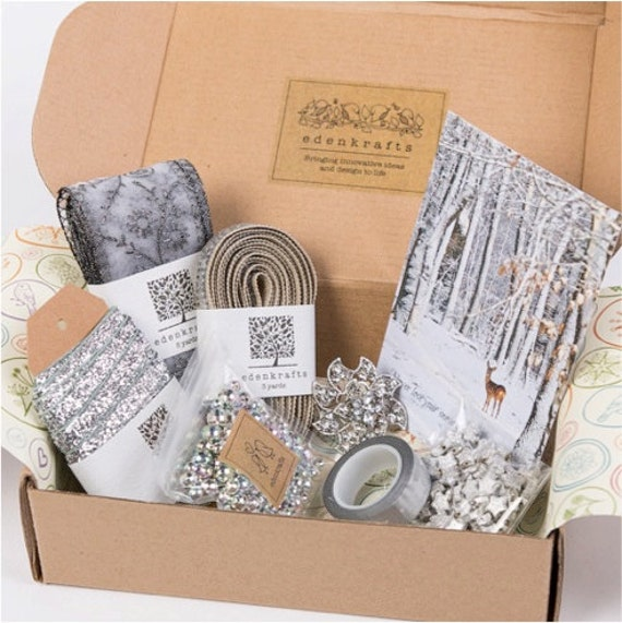 A curated + themed holiday craft box of unique and high quality craft supplies - silver ribbon, trim, beads, pendant, stars
