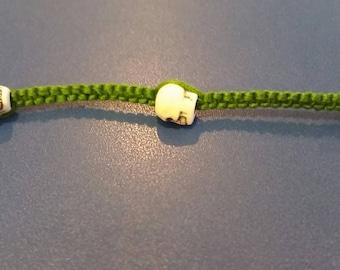 3 White Skulls on Green Cord bracelet