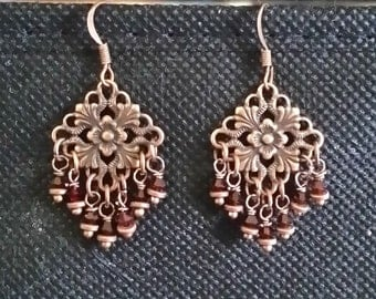 Chandelier earrings of copper and deep red crystals