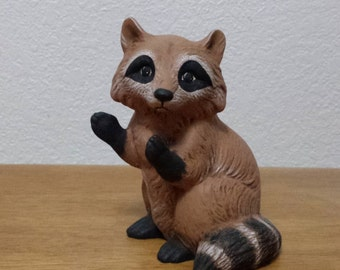 Ceramic Raccoon sitting with arms up just waiting to get into something