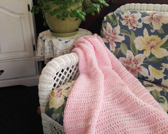 Pink and white crocheted throw blanket