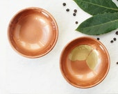 Pair of two small resin salt and pepper spice pinch trinket dish bowls in metalic copper,metalic gold and gold glitter on the bottom.