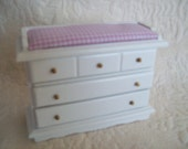 Miniatur, one inch scale, white wooden three drawer change chest with pad on top in lavender and white checked fabric.