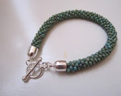 Turquoise blue mottled kumihimo beaded braided bracelet with silver toggle clasp