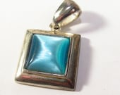 Turquoise blue cats eye pendant. Silver metal square