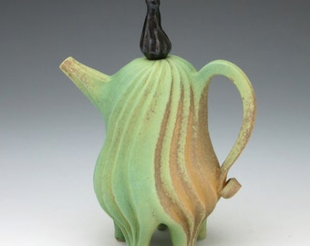 Green and tan porcelain teapot with black lid