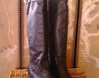 Womens black boots with decorative buckle at the side.