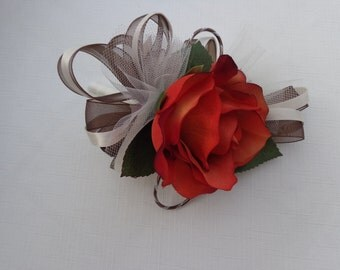 Corsage designed with a rust rose, chocolate and ivory ribbon