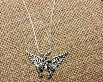 Double gun and wing necklace. On a sterling silver chain. Earrings to match in the shop.