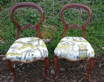 A pair of victorian balloon back chairs
