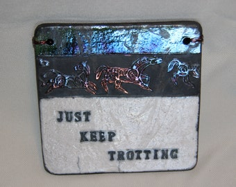 "Clay Quote Tile ""Just Keep Trotting"", varied colors contrast with white background. Black smoke lettering."