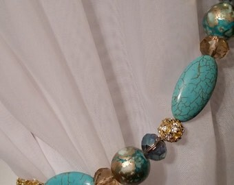 Beaded drapery tie-back with aqua & gold beads, on copper wire.  Fun, beachy and beautiful.  Glam up your curtains!