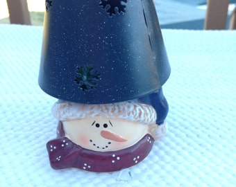 SNOWMAN CANDLE HOLDER is a Vintage Snowman Tea Light Resin Candle Holder with a Blue Punched Tin Lamp Shade with Snowflakes Punched Out