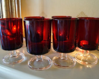 Six deep ruby red coloured cordial or sherry glasses on a clear pedestal. Iconic 70s styling!