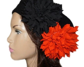Black beret adorned with two big orange and black flowers.