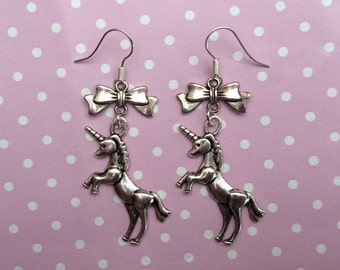 Silver unicorn dangle earrings with silver bows.