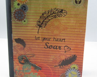 Bound journal with lined paper, steampunk embellishments, and motto, 'Let your heart soar'.'