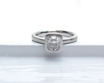 Platinum and cushion cut diamond tapered band solitaire low profile bezel set engagement ring