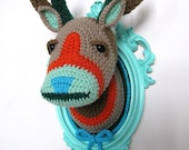 Crochet deer head in a light turquoise frame.