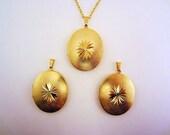 Beautiful golden locket, center starburst pattern. Long gold toned chain. Long necklace. Optional golden or teal blue Swarovski jewel.