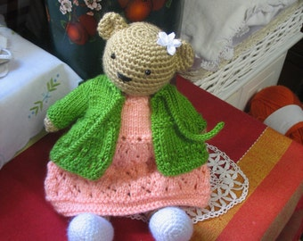 Maggie   A most lovely crochet girl bear that comes with 3 dresses, one knitted cardigan, one skirt one cape and one pair of shoes