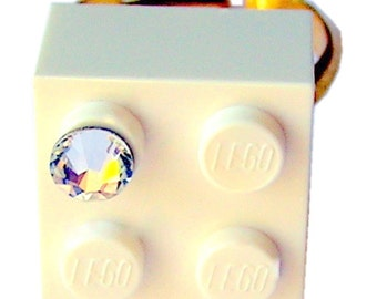 White LEGO (R) brick 2x2 with a Diamond color SWAROVSKI crystal on a Silver/Gold plated adjustable ring finding