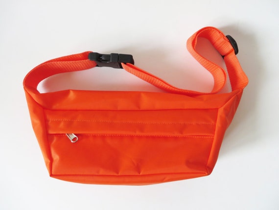 The Bright coral waist pack is fully reflective with an adjustable waist strap for comfort. This style has a zipped main compartment with concealed pockets on the inner.