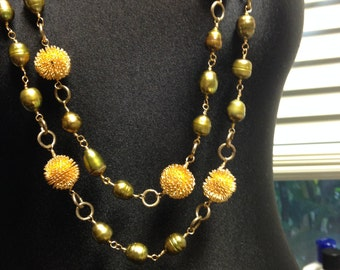 Green Pearls Sunburst . Green pearls and Antique chain with Gold sunburst accent