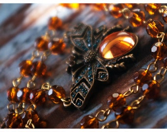 delphine - lovely necklace featuring bejeweled butterfly pendant held captive by crystal beaded chain in shades of amber