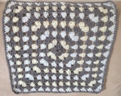 Crochet lap blanket in grey and pastel colours