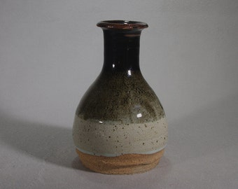 Black and white stoneware vase breaking brown at the lip.