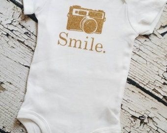 Smile onesie with a camera in gold glitter