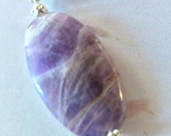 Pendant made with a tumbled natural amethyst with silver fill bail set on a black cord with lobster clasp and extension chain