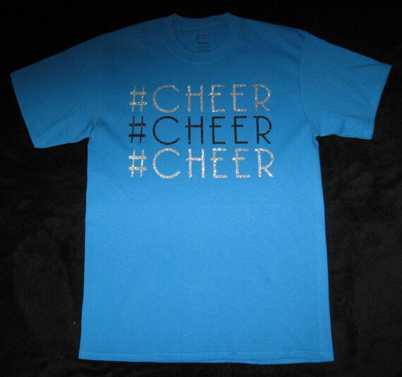Custom Cheer Shirt in Turquoise and is a Medium, #Cheer is on the Front Three times in Silver and Black Glitter