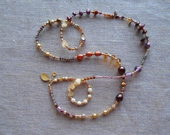 Jewel tone handmade long necklace/purple/amber tones/gold/copper,glass flower beads/fun dangles/glass beads/gold plate/goes with everything