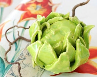 Decorative ceramic artichoke with a little face green glazed