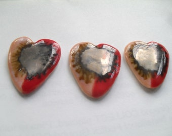 Heart shaped guitar pick-glazed in red and pink with golden center